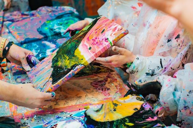 Mãos de crianças derramando tinta acrílica em uma tela