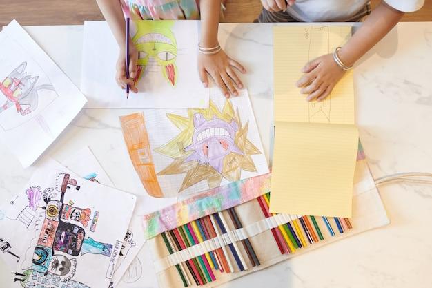 Mãos de crianças desenhando com lápis de cor, vista de cima