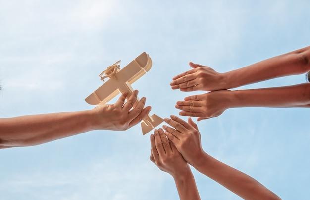 Mãos de crianças e mãos de pai jogando brinquedo avião de madeira em um lindo céu