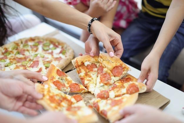 Mãos de crianças e pais pegando uma fatia de pizza closeup