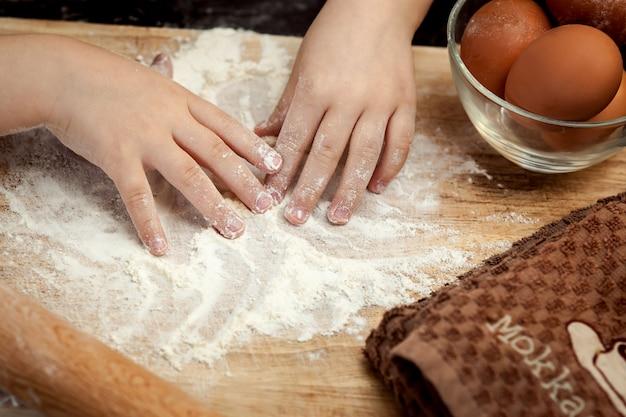 Mãos de crianças em farinha. cozinhar torta de ovo