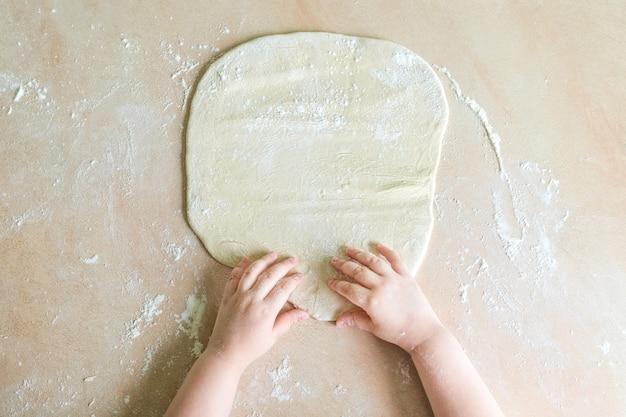 Mãos de crianças fazem massa