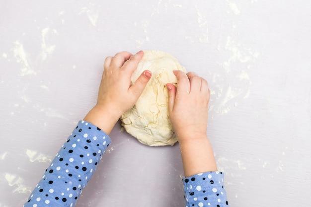 Mãos de crianças fazem uma massa