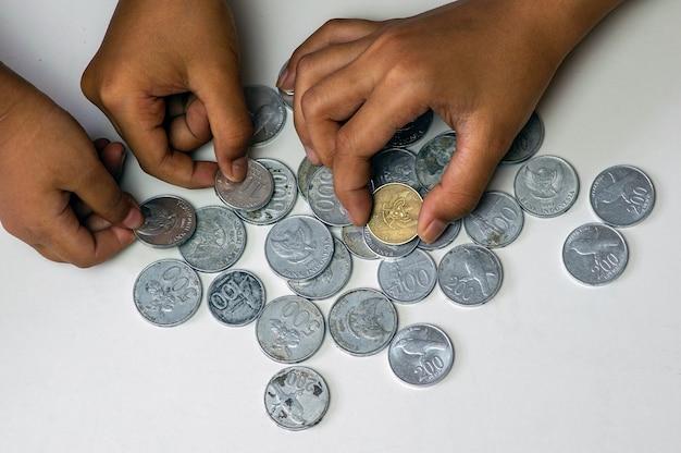 Mãos de crianças indonésias brincando com moedas antigas de rupia