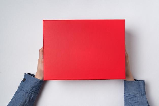 Mãos de crianças mantém uma caixa de presente vermelha. fundo branco.