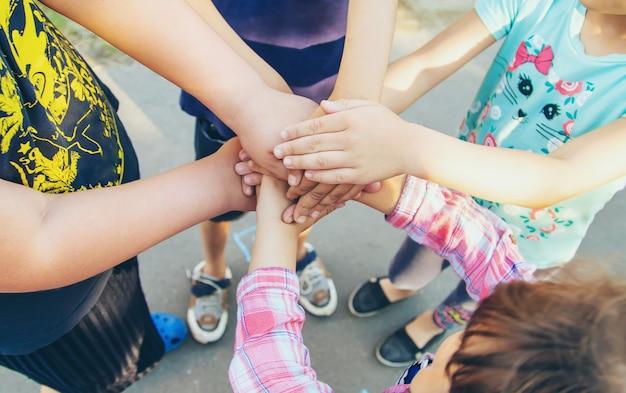 Mãos de crianças, muitos amigos, jogos.