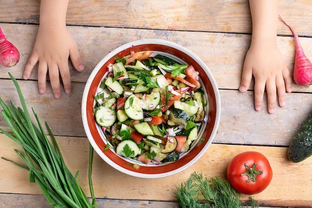 Mãos de crianças preparando salada saudável fresca perto de variedade de legumes e frutas na mesa de madeira, plana leigos