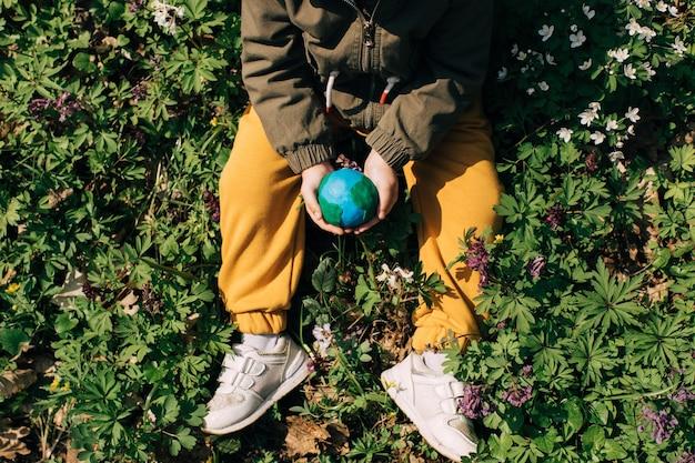 Mãos de crianças segurando a terra contra um fundo verde primavera.