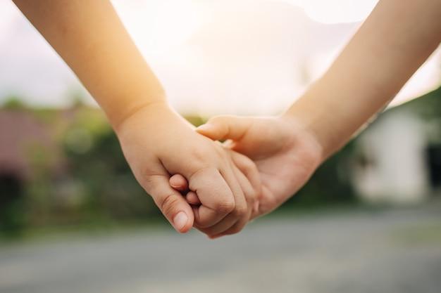 Mãos de crianças segurando juntos conceito de amor e união de irmãos na família