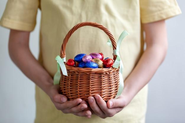 Mãos de crianças segurando ovos de páscoa de chocolate cheio de cesta.
