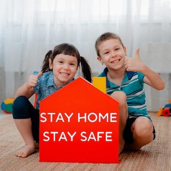 Mãos de crianças segurando um modelo de casa vermelha com palavras