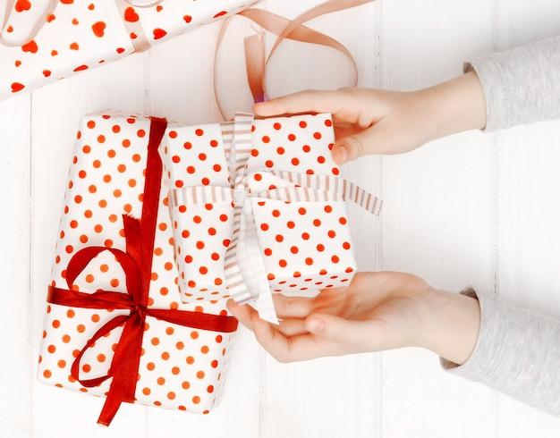 Mãos de crianças segurando uma caixa de presente