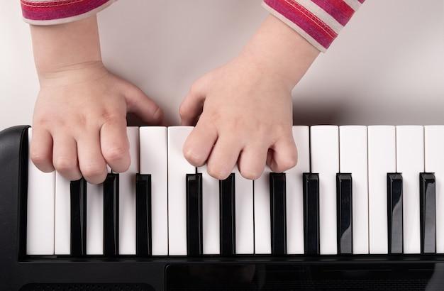 Mãos de crianças tocando piano vista superior, conceito de educação.