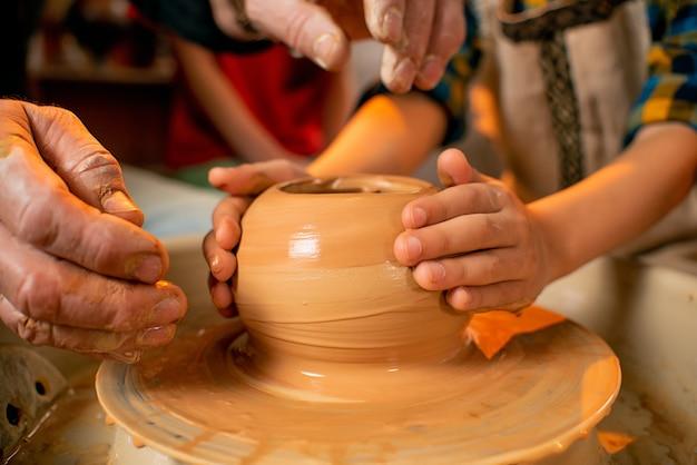 Mãos de crianças trabalham com argila em uma máquina especial.