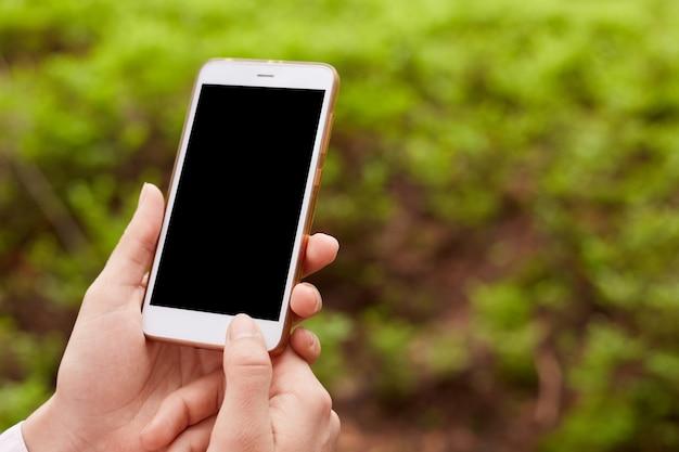 Mãos de desconhecido segurando o dispositivo moderno, sendo em torno da natureza, tela preta, desligando o smartphone, sem conexão na floresta, usando o celular na vida cotidiana