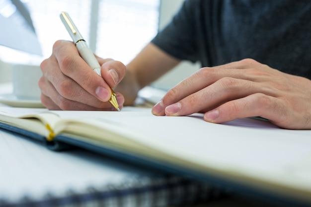 Mãos de designer gráfico homem escrevendo em um diário