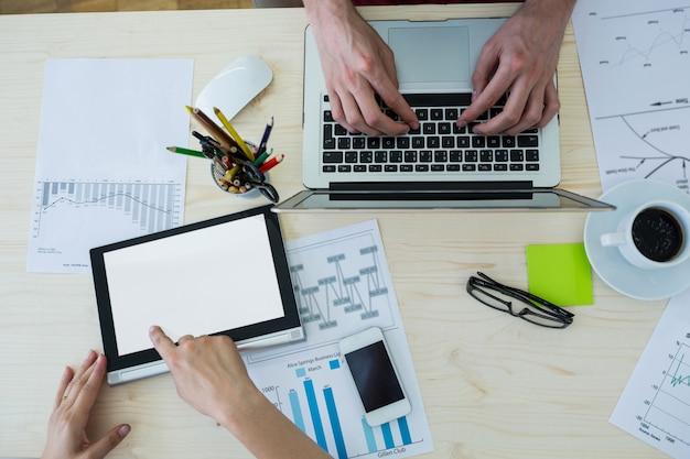 Mãos de designers gráficos que usam o portátil e tabuleta digital