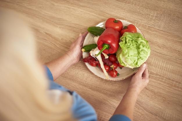 Mãos de dieta de perda de peso de legumes de oferta de mulher.