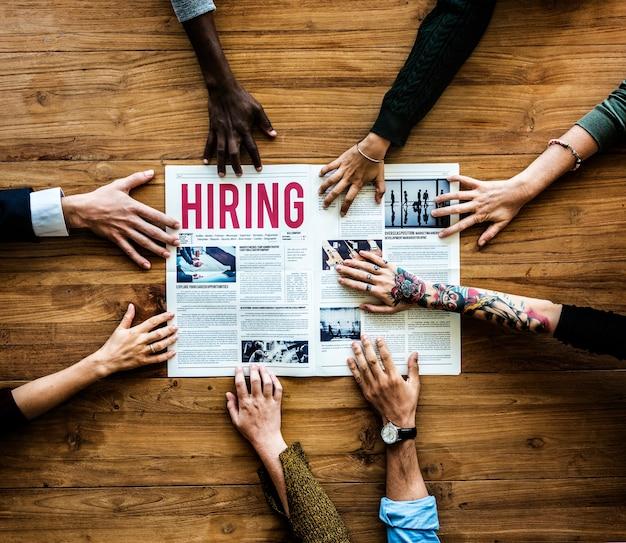Mãos de diversas pessoas estendem a mão para a contratação de anúncio de jornal