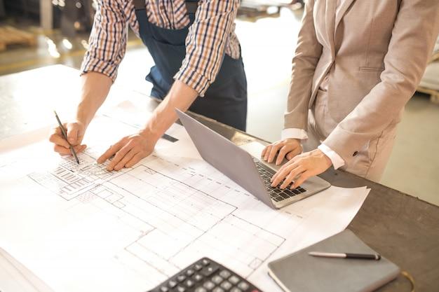 Mãos de dois engenheiros profissionais em trajes de trabalho, curvando-se sobre a mesa enquanto discutia o esboço na planta