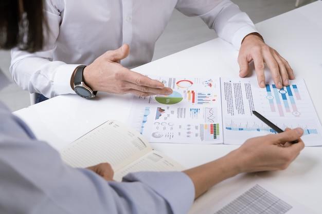 Mãos de dois gerentes financeiros sobre documentos durante a discussão de gráficos, tabelas e diagramas na reunião de trabalho