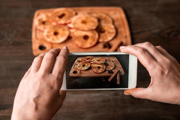 Mãos de dona de casa com smartphone tirando foto de fatias de maçã fresca polvilhadas com canela em pó na placa de madeira e mesa