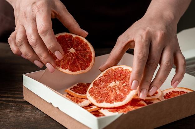 Mãos de dona de casa contemporânea de meia-idade colocando fatias de laranja ou grapefruit secas caseiras em uma pequena caixa de papelão quadrada