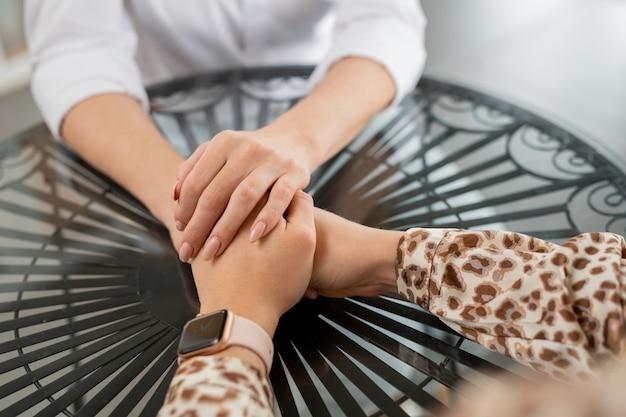 Mãos de duas jovens amigas se apoiando enquanto se sentam à mesa redonda em um café, relaxando e se comunicando