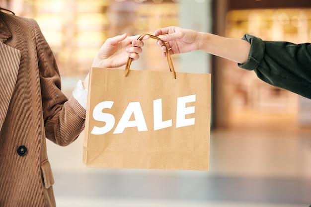 Mãos de duas jovens consumidoras contemporâneas segurando a sacola de papel pelas alças enquanto estão dentro do centro comercial na sexta-feira negra