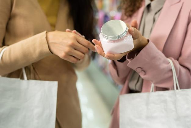 Mãos de duas jovens consumidoras elegantes com sacolas de papel escolhendo creme para o corpo enquanto seguram o testador e decidem se compram ou não
