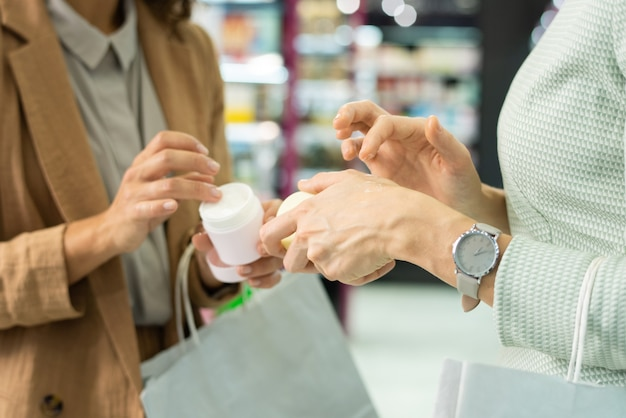 Mãos de duas jovens consumidoras elegantes com sacos de papel aplicando creme cosmético enquanto o testam em um salão de beleza e escolhem o que comprar