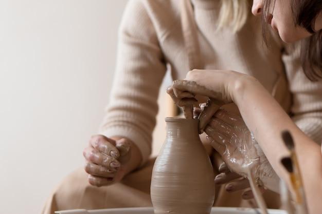 Mãos de duas lindas mulheres trabalhando juntas com a roda de oleiro na escola de cerâmica