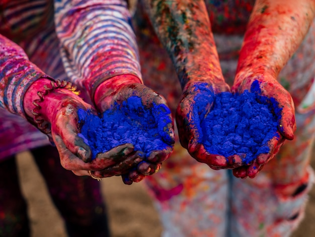 Mãos de duas meninas nas mãos da tinta