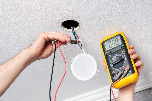 Mãos de eletricista consertam ou instalam com uma chave de fenda a moderna lâmpada led Foto Premium