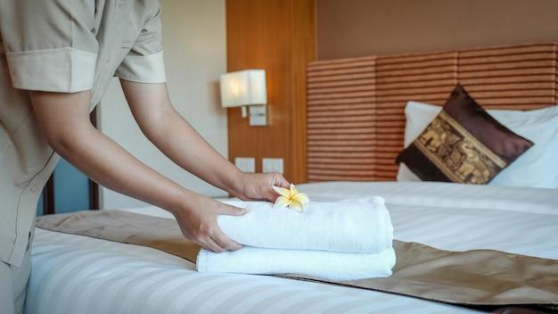 Mãos de empregada de hotel colocando flores de plumeria e toalhas na cama em um quarto de hotel de luxo
