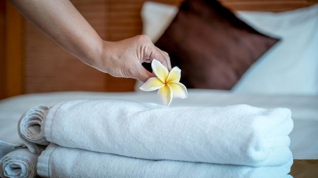 Mãos de empregada de hotel colocando flores de plumeria e toalhas na cama no quarto do hotel de luxo, prontas para viagens turísticas.
