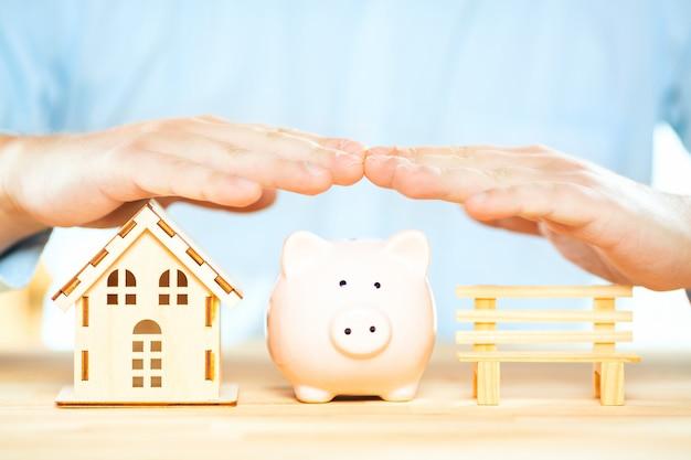 Mãos de empresário acima de um cofrinho, modelo de casa e um banco.