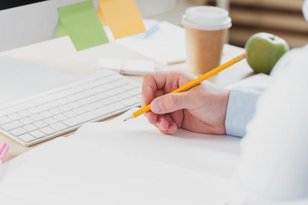 Mãos de empresário com caneta escrevendo caderno na mesa da mesa de escritório.