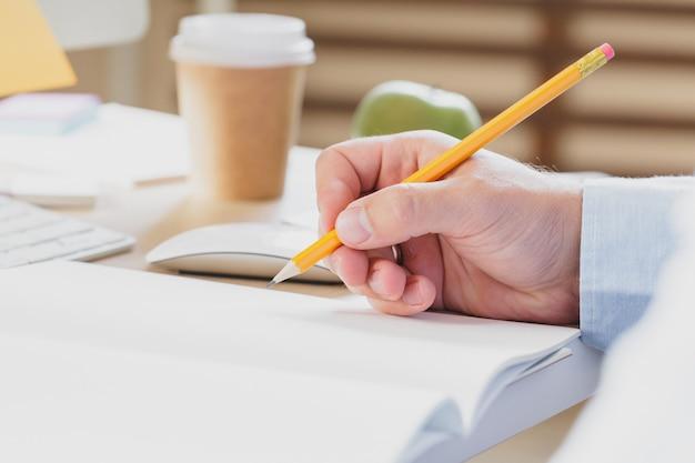 Mãos de empresário com caneta escrevendo o caderno na mesa da mesa de escritório, conceito do negócio