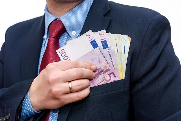 Mãos de empresário escondendo notas de euro no bolso