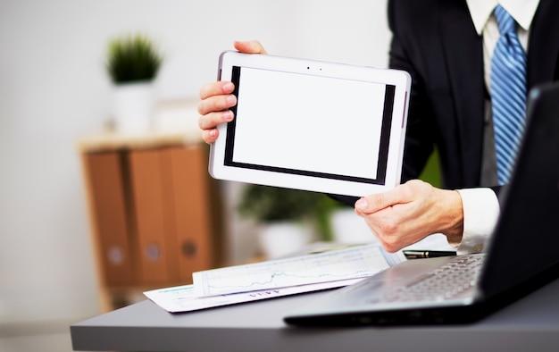 Mãos de empresário estão segurando o dispositivo de tela de toque.