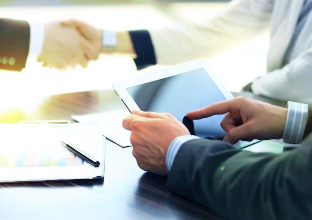 Mãos de empresário tocando espaço de cópia de tela vazia do tablet digital, aperto de mão durante a reunião.