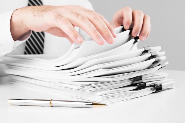 Mãos de empresário trabalhando em pilhas de arquivos de papel para pesquisar informações, negócios e conceito financeiro.