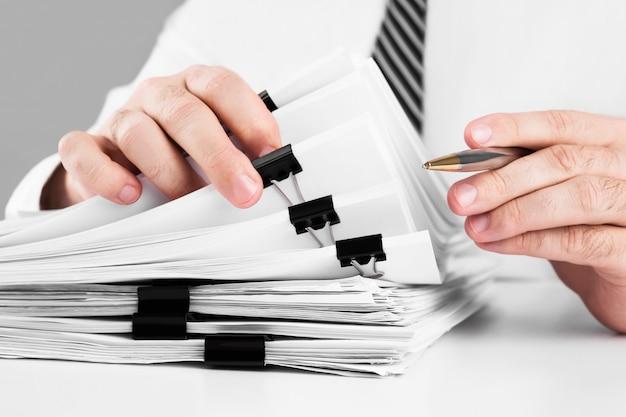 Mãos de empresário trabalhando em pilhas de arquivos de papel para pesquisar informações