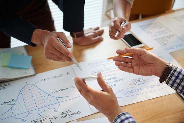 Mãos de empresários analisando gráficos com várias estatísticas e dados ao trabalhar na estratégia de marketing