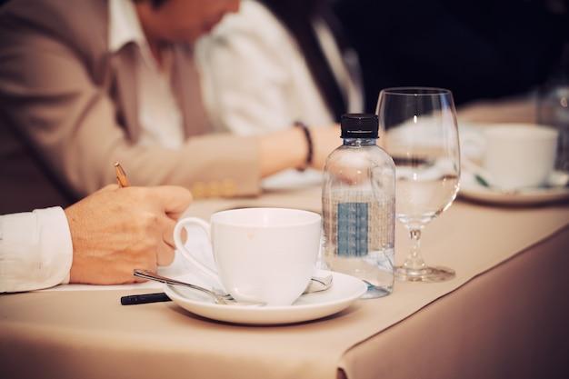 Mãos de empresários com caneta ou lápis, papéis e xícaras de café na sala de seminário