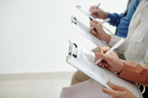 Mãos de empresários preenchendo formulários impressos de curriculum vitae antes da entrevista de emprego