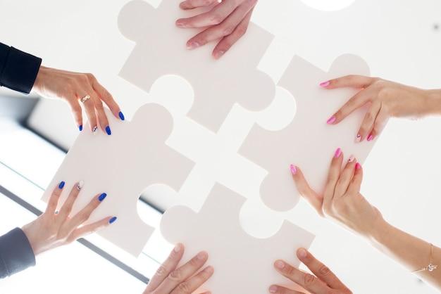 Mãos de empresários segurando um quebra-cabeça branco