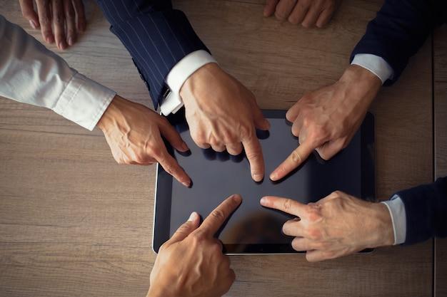 Mãos de empresários tocando da tela do tablet digital. trabalho em equipe para o sucesso. vista do topo