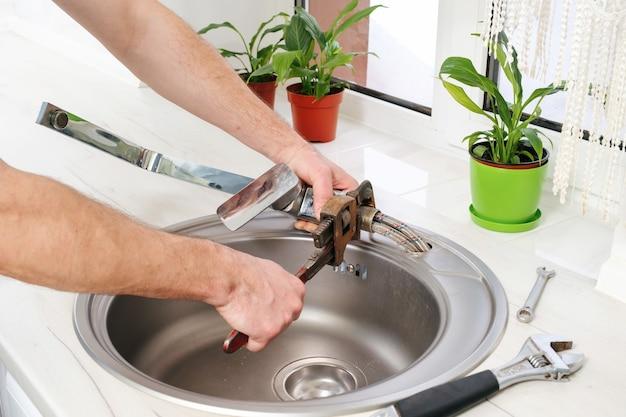 Mãos de encanador removem a velha torneira da pia com uma chave ajustável